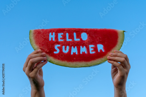 Obraz A piece of watermelon against a blue sky. Children's hands are holding a slice of watermelon with the text Hello Summer. Summer time concept - fototapety do salonu