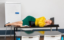 The Teacher Is Tired And Go To Sleep On The Desktop In The Classroom