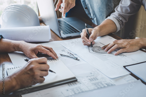Fototapety, obrazy: Construction and structure concept of engineer working drawing on blueprint meeting for project working with partner on model building and engineering tools in working site, construction concept