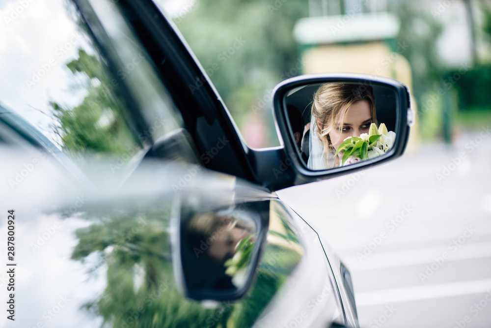Fototapeta reflection of attractive and blonde bride smelling bouquet in car