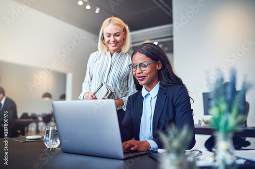 Cuadros en Lienzo Smiling businesswomen looking at something on a laptop at work