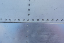 Aluminum Surface Of The Aircraft Fuselage. Smooth Rows Of Rivets, There Are Scratches, Dirt