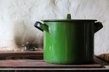 Old Enameled Green Pan (saucepan) With A Lid On A Cast-iron Stove. Rustic Cuisine