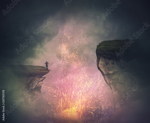 Surreal scene as a fearless man stand on the edge of a cliff watching the magical fire sparkles eruption as from a volcano crater Canvas Print