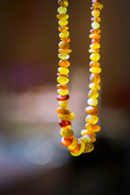 Natural Amber Beads Shining On Sun Close Up. Handmade Souvenir Of Real Gems On A Dark Background, Selective Focus