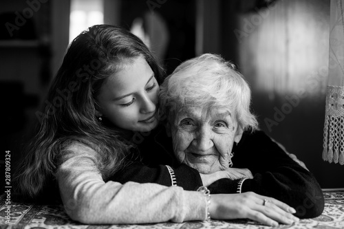 Fotografie, Tablou Portrait of an elderly gray-haired woman with her beloved granddaughter