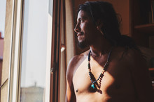 Native American Man With Mineral Stone Dolphin Pendant Necklace Jewelry Looking Out From His Window