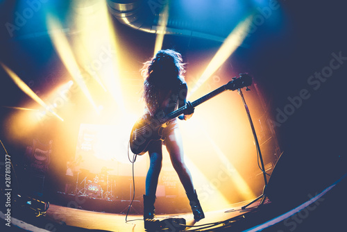 Silhouette of an unrecognizable woman playing the electric guitar - 287810377