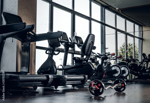 Poster Fitness New empty gym club with different type of training apparatuses and big window.