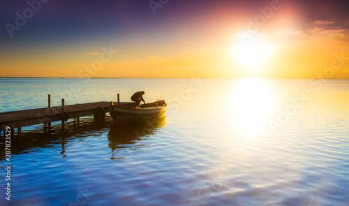 Foto auf AluDibond Pier hombre solitario en su barca en el lago