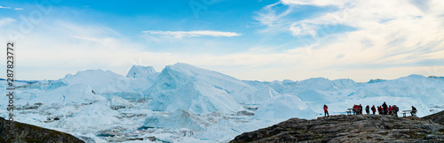 Fotomural Icebergs in arctic landscape nature with travel tourists in Greenland