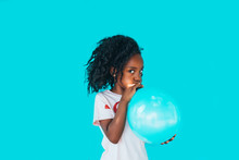 Little Girl In Front Of A Blue Wall, Blowing Up Balloon