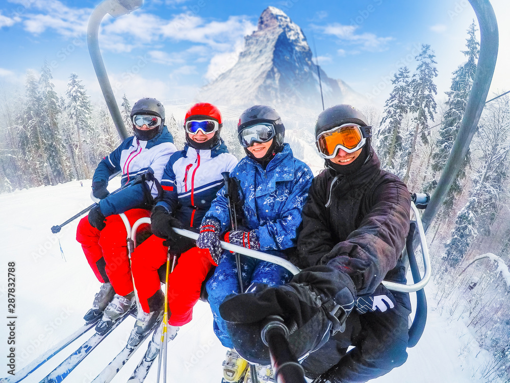 Fototapeta amazing beautiful view ski resort in Switzerland with cable chairlift transport Cheerful young friends skiers on ski lift