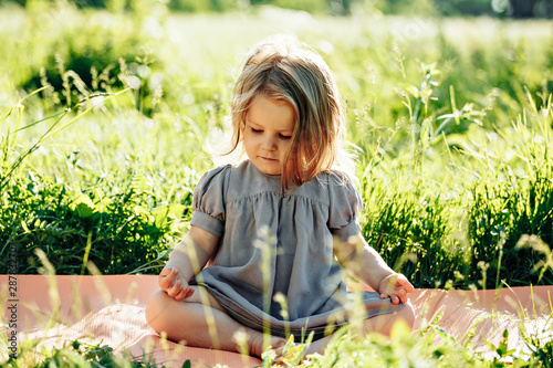 baby yoga Lotus pose.. a child practicing yoga outdoors