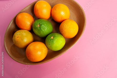 Clay bowl, rustic, handcrafted, with orange, lemon fruit. Cassis color background. From above. Text space.