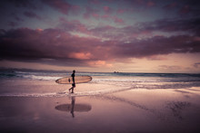 Surfer With Surfboard On Beach At Dawn