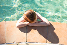 Top Angle View Of Girl Leaning On The Side Of Swimming Pool