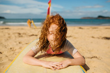 Girl Laying On Surfboard At Beach