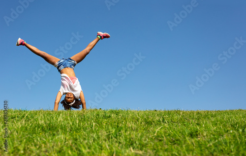 Young black girl stand on hands over blue sky