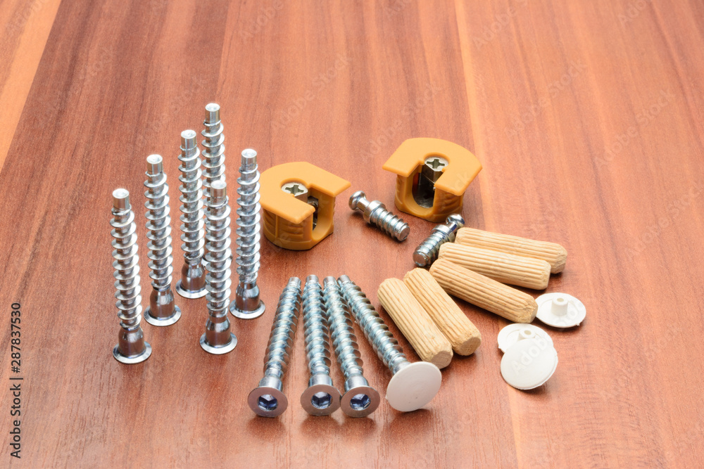 Fototapety, obrazy: Euro screws, dowels, ties, chrome-plated pipe and console are laid out on a wooden panel