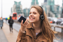 Happy Young Woman With Headphones And Cell Phone In The City, London, UK