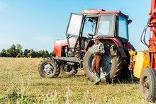 Selective Focus Of Bearded Farmer In Straw Hat Using Laptop Near Tractor
