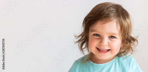 Beautiful happy toddler child girl smiling, portrait neutral background, space f Canvas Print