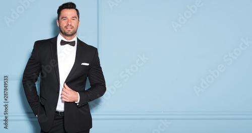 Valokuvatapetti Elegant man in black classic suit posing in nice studio.