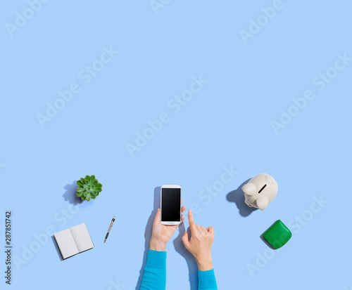 Fototapeta Person using a smartphone with a piggy bank obraz