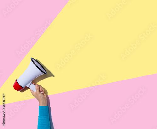 Obraz Person holding a megaphone with hard shadow - fototapety do salonu