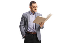 Young Man With Glasses Standing And Reading A Book