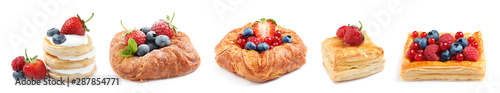 Fototapeta Set of fresh delicious puff pastries with sweet berries on white background