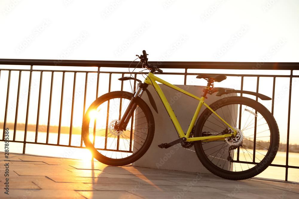 Fototapeta Yellow bicycle parked near railing on city waterfront at sunset