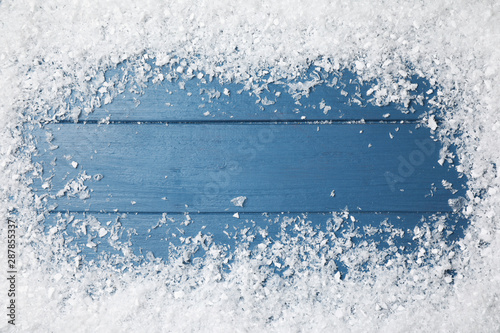Foto auf Leinwand Texturen Frame of white snow on blue wooden background, top view with space for text. Christmas season