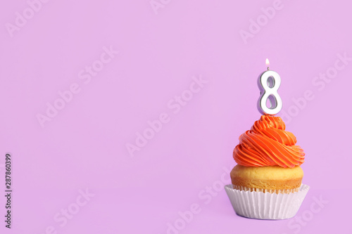 Photo  Birthday cupcake with number eight candle on violet background, space for text