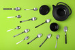 Leinwanddruck Bild - Flat lay composition of spoons, cup and teapot on green background