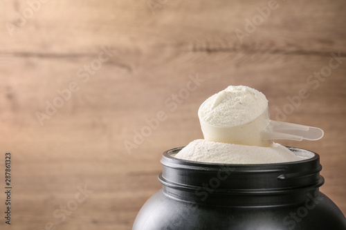 Black jar with measuring scoop of protein powder against wooden background Fototapeta