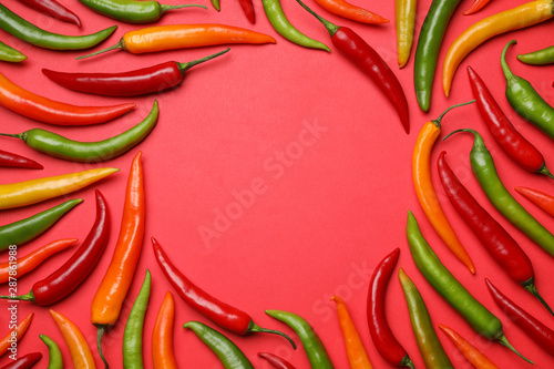 Photo  Frame made with different chili peppers on red background, flat lay