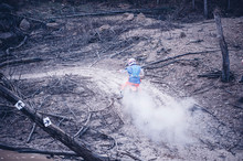 Motocross Rider Running In A Large Cloud Of Dust And Debris Mud And WaterMotocross Rider Running In A Large Cloud Of Dust And Debris Mud And Water