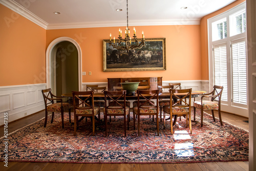 Fotomural  Orange peach colorful dining room with oriental rug and classic wood chairs and table with chandelier and artwork