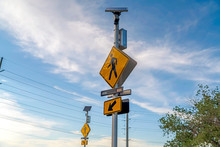 Pedestrian Crossing And Arrow Signs Viewed Against Cloudy Blue Sky