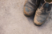 Worn Out Work Boots On Concret...