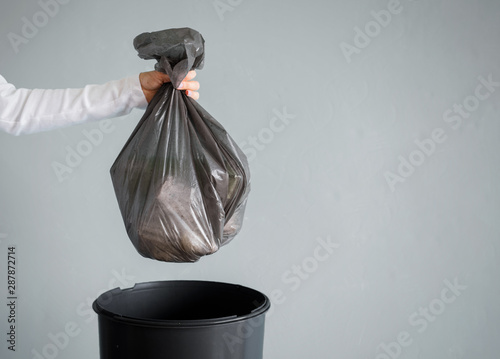 Photo Person throwing out garbage in plastic bag