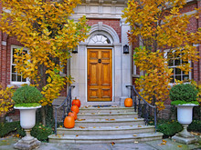 Front Steps Of Large Brick House With Pumpkins