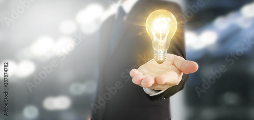Fototapeta Hand of holding illuminated light bulb obraz na płótnie