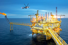 Offshore Oil And Gas Rig Platform With Offshore Helicopter Transporting To Oil Rig At Beautiful Sky In The Gulf Of Thailand.