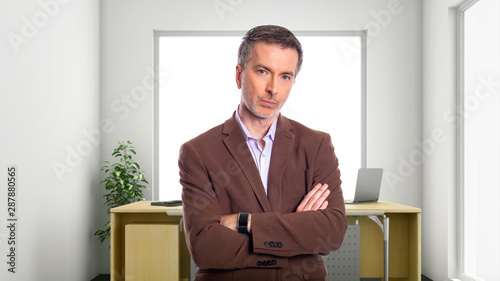Middle-Aged businessman with gray hair and wearing a brown jacket standing in an office Canvas Print