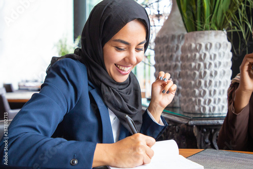Fotomural  Happy businesswoman taking notes in coffee shop