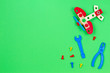 canvas print picture - Toy wooden plane, bolts and toys tools on green background