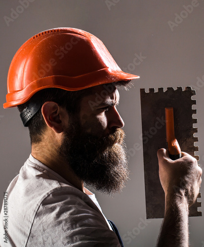 Plastering tools. Tool, trowel, handyman, man builder. Mason tools, builder. Builders in hard hat, helmet. Bearded man worker, beard, building helmet, hard hat